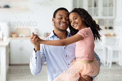Emotional black father and daughter dancing waltz at home