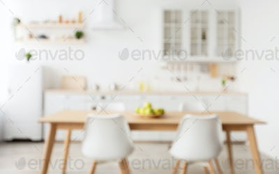 Comfortable light kitchen and stylish cozy design. Blurred background with wooden dining table and