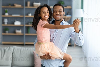 Cheerful african american father dancing with his little daughter