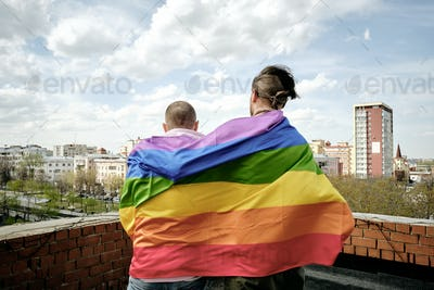Rear view of two gay men wrapped into lgbtq flag