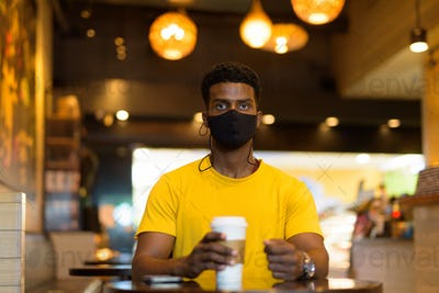 Portrait of handsome black African man wearing yellow t-shirt in coffee shop