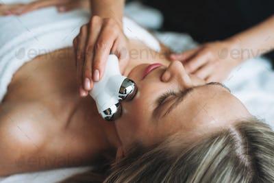Woman enjoys facial massage with microcurrent facial massager in spa salon