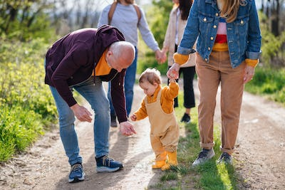 Small toddler with unrecognizable parents and grandparents on a walk outdoors in nature