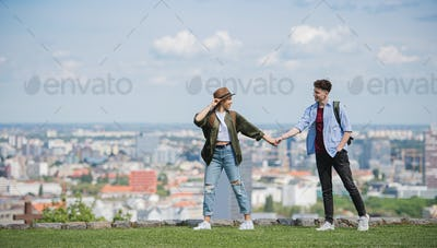 Young couple travelers with map in city on holiday walking and holding hands
