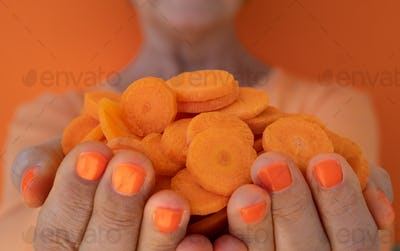 Mature woman's hands full of round sliced carrots. Orange background