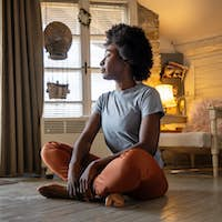 Health lifestyle and people concept. Portrait of peaceful young black woman meditating indoors
