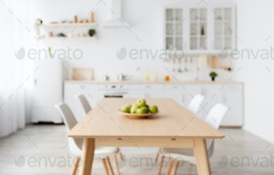 Blurred photo of scandinavian classic kitchen with wooden and white details. Dining table and light