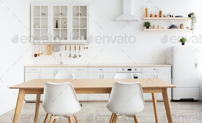 Modern design scandinavian kitchen. White kitchen furniture and dining table with chairs, utensils