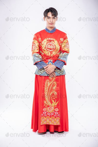 Man wear Cheongsam smile to welcome traveller shopping in chinese new year