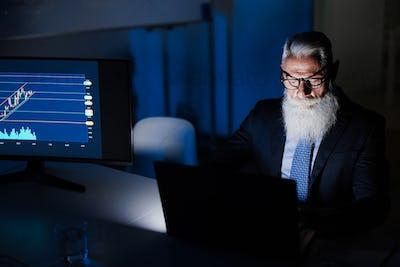Senior business man working at night inside fintech office - Focus on face