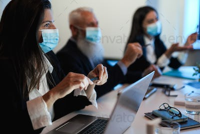 Business teamwork doing meeting while wearing safety mask - Focus on woman left hand