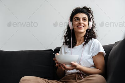 Joyful brunette woman in headphones eating cereal while sitting on sofa