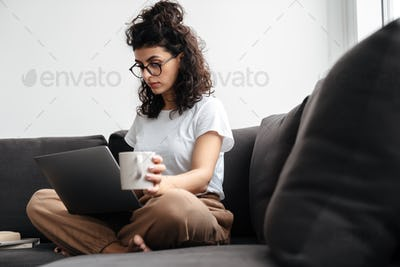 Serious brunette young woman working with laptop and drinking coffee