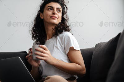 Happy brunette young woman working with laptop and drinking coffee
