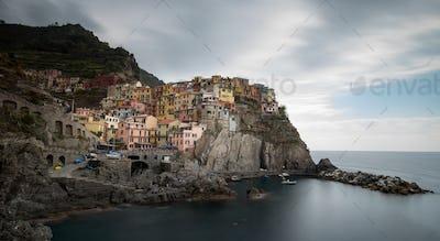 Village of Manarola with colourful houses at the edge of the cliff Riomaggiore, Cinque Terre