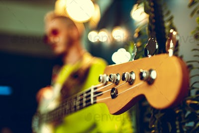 Guitar head with .ring gear on blurred guitarist background