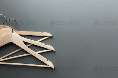 Black Friday or clothing industry concept on gray background with wooden hangers
