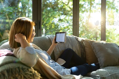 Asian woman chatting using tablet with blank screen, sitting on sofa at home