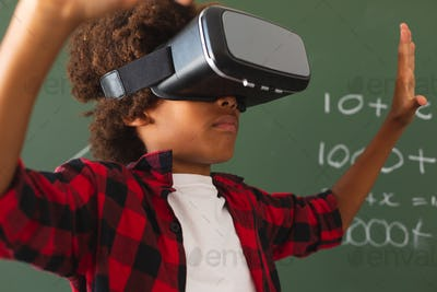 African american schoolboy in front of chalkboard in classroom using vr headset