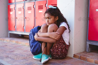 Unhappy african american schoolgirl sitting by lockers in school corridor with schoolbag