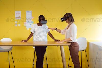 Diverse businesswomen standing at desk using vr headset at work