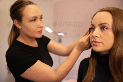 Female Specialist Using Mascara On Customer's False Eyelashes