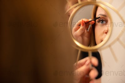Woman Holding Mirror While Female Cosmetologist Using Mascara