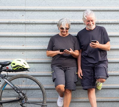 Two senior people bikers gray haired resting close to their electric bicycles using mobile phones.