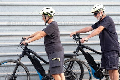 Elderly couple of people with yellow helmet ready to start ride with electro bicycles. Healthy life
