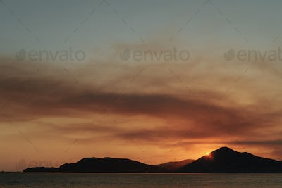Orange sunset at the sea with mountains silhouettes, Montenegro