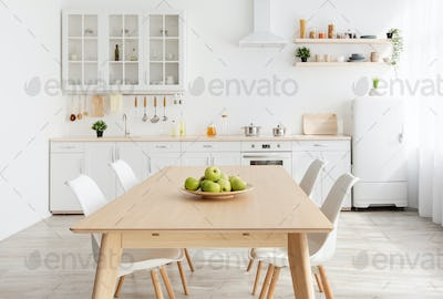 Scandinavian contemporary style kitchen with eating area and simplistic accents. Wooden table and