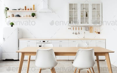 Scandinavian interior design. Light kitchen furniture and dining table, different utensils and