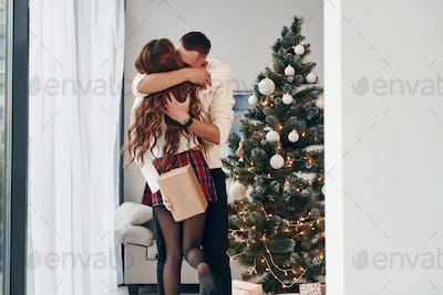Woman makes surprise for man. Young romantic couple celebrates New year together indoors