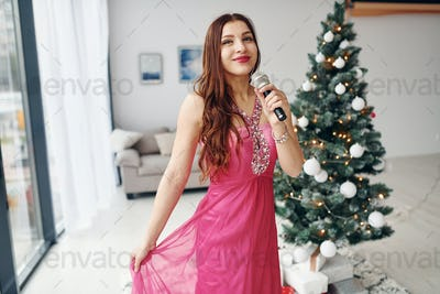 Beautiful woman in pink dress singing indoors at New year party