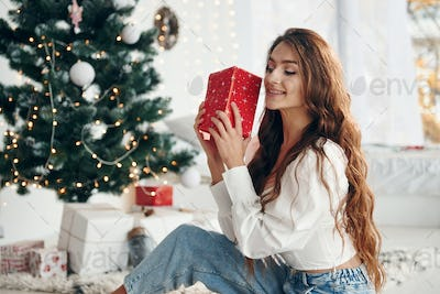 Happy young woman sits indoors near christmas tree and celebrates New year