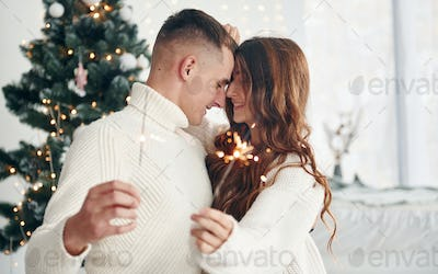 With sparklers in hands. Young romantic couple celebrates New year together indoors