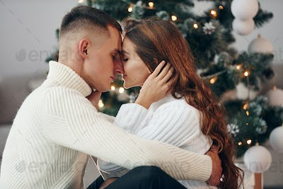 Closeness of the people. Young romantic couple celebrates New year together indoors