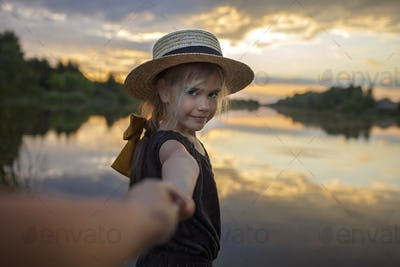 Girl in summer straw hat pulling hand forward to sunset on lake, lifestyle, local travel