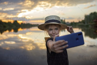 Girl in summer straw hat taking selfie for cellphone at sunset on lake, lifestyle, local travel