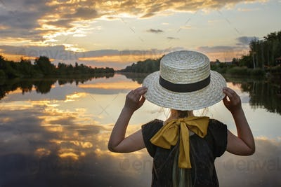 Girl in summer straw hat looking at sunset on lake, lifestyle, local travel, back view