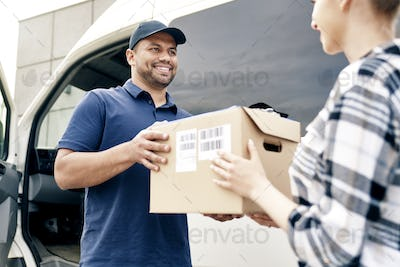Delivery person giving boxes to woman
