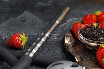 Hookah parts and strawberry on gray surface close up