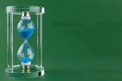 Sand hourglass on dark green paper background