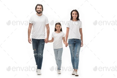 smiling family in white shirts and jeans holding hands while walking together isolated on white