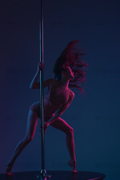 seductive athletic woman dancing with pole on blue
