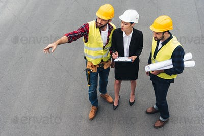 overhead view of female engineer and male workers with clipboard and blueprints pointing at
