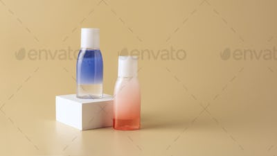 close up view of face wash in bottles on white cube on beige backdrop