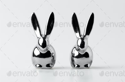 two statuettes of easter rabbits on white
