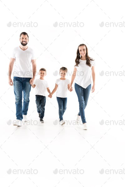 smiling family holding hands while walking together isolated on white