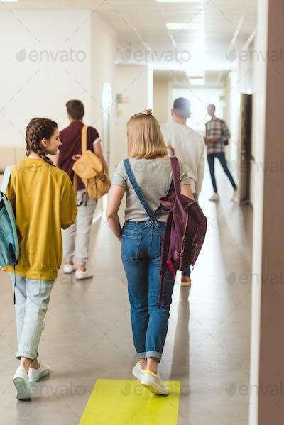 rear view of high school students walking by school corridor